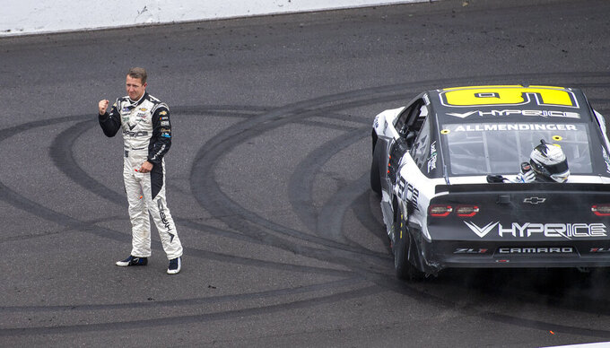AJ Allmendinger (16) reacts on the track after winning a NASCAR Cup Series auto race at Indianapolis Motor Speedway, Sunday, Aug. 15, 2021, in Indianapolis. (AP Photo/Doug McSchooler)