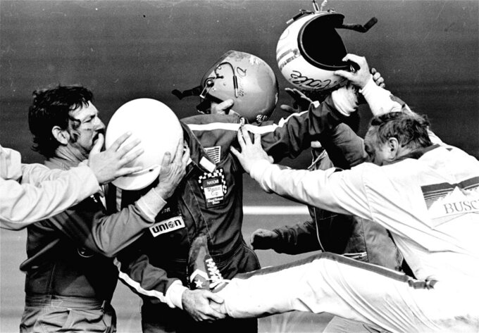 FILE - In this Feb. 18, 1979, file photo, Cale Yarborough, right, kicks and pushes Bobby Allison, center, who is catching his leg as brother Donnie, left, tries to pull his Bobby free from the fight which started after Yarborough collided with Donnie on the last lap of the Daytona 500 auto race, taking them both out of the finals in the race in Daytona Beach, Fla. The 1979 race was instrumental in broadening NASCAR's southern roots. Forty years later, it still resonates as one of the most important days in NASCAR history. (AP Photo/Ric Feld, File)