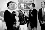 FILE - Los Angeles Raiders coach Tom Flores clutches the Super Bowl trophy as Raiders managing general partner Al Davis is interviewed by Brent Musburger in the locker room after their 38-9 win over the Washington Redskins in Super Bowl XVIII at Tampa Stadium, in this Jan. 23, 1984, file photo. At right is NFL Commissioner Pete Rozelle.  The AFL gave Flores one last chance when the fledging league launched in 1960 and Flores seized the opportunity. He became the original quarterback of the Raiders before going on to a trailblazing career as a coach and executive that landed him in the Pro Football Hall of Fame following a lengthy wait. (AP Photo/File)