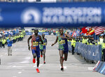 Lawrence Cherono, left, of Kenya, runs to the finish line to win the 123rd Boston Marathon in front of Lelisa Desisa, of Ethiopia, right, on Monday, April 15, 2019, in Boston. (AP Photo/Winslow Townson)