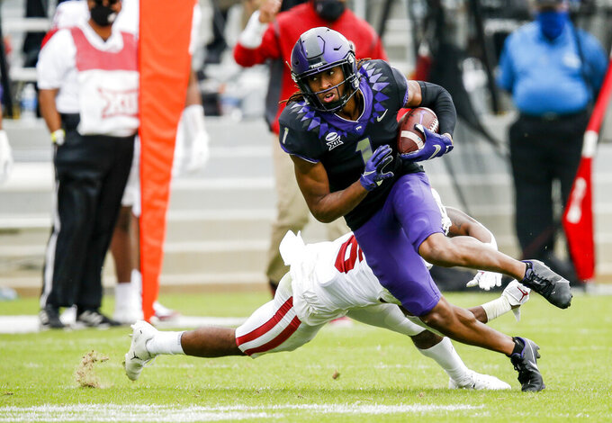 TCU wide receiver Quentin Johnston (1) evades a tackle from Oklahoma cornerback Tre Brown (6) during the second half of an NCAA college football game, Saturday, Oct. 24, 2020, in Fort Worth, Texas. (AP Photo/Brandon Wade)