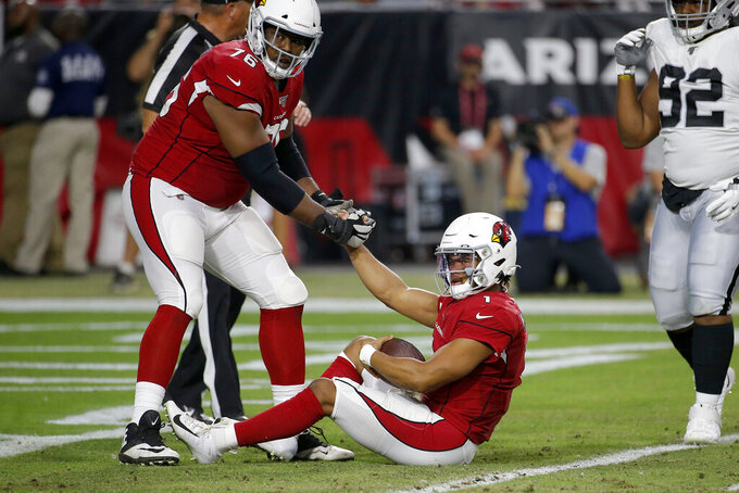 Arizona Cardinals quarterback Kyler Murray (1) is helped up by offensive tackle Marcus Gilbert (76) after being sacked for a safety against the Oakland Raiders during the first half of an an NFL football game, Thursday, Aug. 15, 2019, in Glendale, Ariz. (AP Photo/Rick Scuteri)