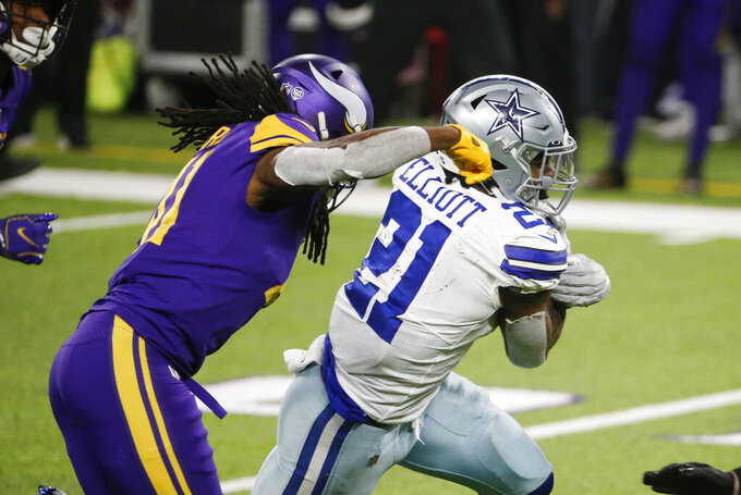 Dallas Cowboys running back Ezekiel Elliott (21) runs from Minnesota Vikings safety Anthony Harris, left, during the second half of an NFL football game, Sunday, Nov. 22, 2020, in Minneapolis. The Cowboys won 31-28. (AP Photo/Bruce Kluckhohn)