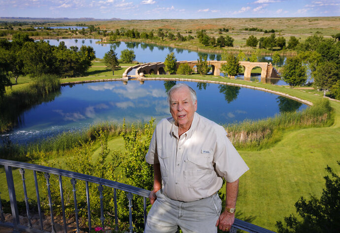 FILE - In this May 30, 2017, file photo, oil tycoon T. Boone Pickens poses for a photo on his Mesa Vista Ranch in the panhandle of Texas. An ornate conference-room table where the late legendary oil tycoon Pickens made billion-dollar deals and hosted VIPs in his Dallas office is heading to the Oklahoma State Capitol. Officials at Oklahoma State University announced Wednesday, oct 9, 2019, the 24-foot-long table and 22 leather chairs will be loaned to the governor's office for the next 10 years. (Tom Fox/The Dallas Morning News via AP, File)