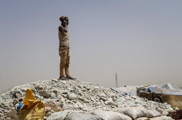 In this photo taken Sunday, Feb. 23, 2020, a miner stands on a mound of dirt to make a phone call, at a gold mine in Bouda, Burkina Faso. A growing number of small-scale gold miners are out of work in Burkina Faso as jihadists try to seize control of the country's most lucrative industry. (AP Photo/Sam Mednick)