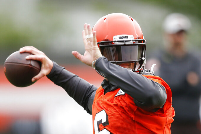 FILE - In this May 22, 2019, file photo, Cleveland Browns' Baker Mayfield throws a pass during an NFL football practice at the team's training facility in Berea, Ohio. It all starts with Mayfield, the former No. 1 overall pick who began last season as Tyrod Taylor's backup and finished it breaking Peyton Manning's league rookie record for touchdown passes despite playing in only 14 games. (AP Photo/Ron Schwane, File)