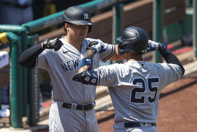 New York Yankees' Gleyber Torres (25) celebrates his solo home run with Luke Voit during the seventh inning of a baseball game against the Washington Nationals at Nationals Park, Sunday, July 26, 2020, in Washington. (AP Photo/Alex Brandon)