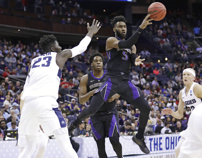 Washington's Jaylen Nowell (5) passes against Utah State's Neemias Queta (23) in the first half during a first round men's college basketball game in the NCAA Tournament in Columbus, Ohio, Friday, March 22, 2019. (AP Photo/Tony Dejak)