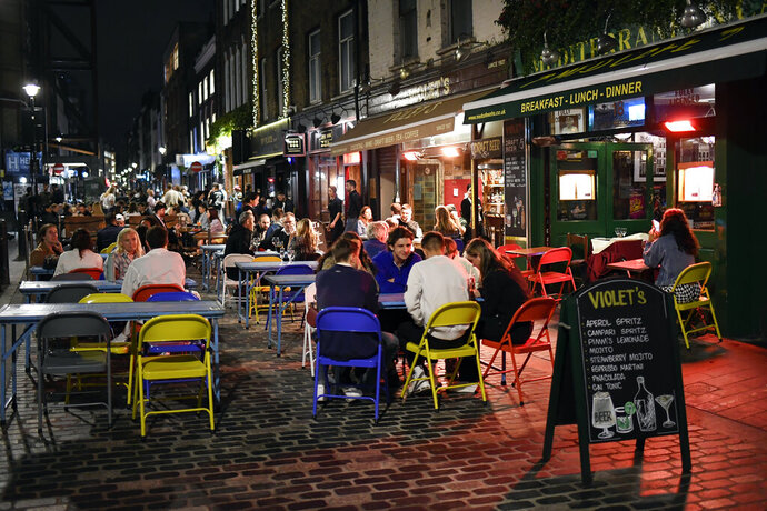 People eat and drink outside in Soho, in London, Tuesday, Sept. 22, 2020. Britain's Prime Minister, Boris Johnson, has announced that pubs and restaurants closing at 10pm, due to the spike of cases of coronavirus across the United Kingdom. (AP Photo/Alberto Pezzali)
