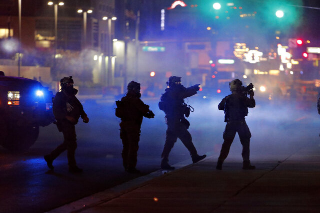 FILE - In this May 30, 2020, file photo, police walk through tear gas as they try to disperse protesters in Las Vegas. Three Nevada men with ties to a loose movement of right-wing extremists advocating the overthrow of the U.S. government have been arrested on terror charges in what authorities say was a conspiracy to spark violence during recent protests in Las Vegas. (AP Photo/John Locher, File)