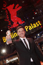 Director Francois Ozon holds aloft the Silver Bear grand jury prize for the film 'By the Grace of God' after the award ceremony of the 2019 Berlinale Film Festival in Berlin, Germany, Saturday, Feb. 16, 2019. (AP Photo/Markus Schreiber)