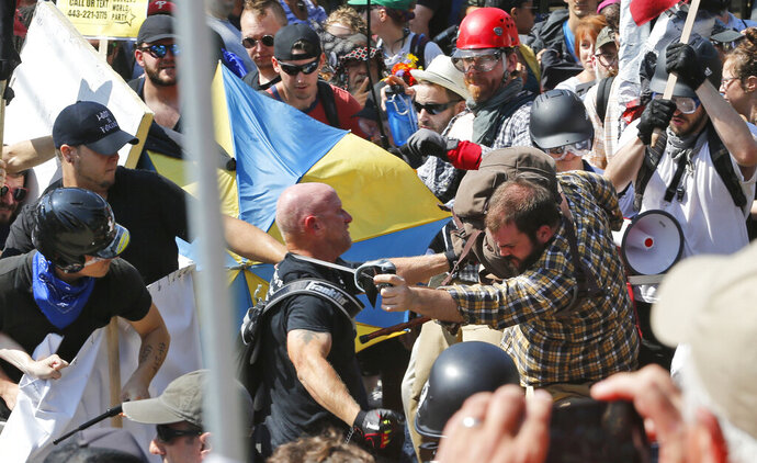 FILE - In this Aug. 12, 2017 file photo, white nationalist demonstrators clash with counter demonstrators at the entrance to Lee Park in Charlottesville, Va. Cole Evan White, 26, who pleaded guilty to attacking counterprotesters at a white nationalist rally in Virginia has been a student at San Francisco State University in California while awaiting his sentencing in federal court. A spokesman for the school confirmed Monday, Oct. 12, 2020 that White is currently a part-time student who first enrolled in the fall 2017 semester. (AP Photo/Steve Helber, File)