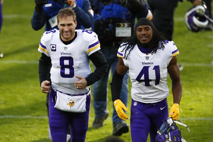 Minnesota Vikings' Kirk Cousins (8) and Anthony Harris (41) smile as they run off the field after an NFL football game Sunday, Nov. 1, 2020, in Green Bay, Wis. The Vikings won 28-22. (AP Photo/Matt Ludtke)