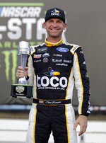 Clint Bowyer poses with the award in Victory Lane after winning the pole position for Saturday's NASCAR All-Star auto race during qualifying at Charlotte Motor Speedway in Concord, N.C., Friday, May 17, 2019. (AP Photo/Chuck Burton)