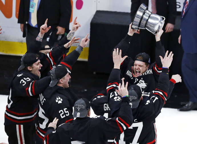 Northeastern defenseman Eric Williams, right, hoists the championship trophy after defeating Boston College 4-2 in the NCAA hockey Beanpot tournament final game in Boston, Monday, Feb. 11, 2019. Northeastern won 4-2. (AP Photo/Charles Krupa)