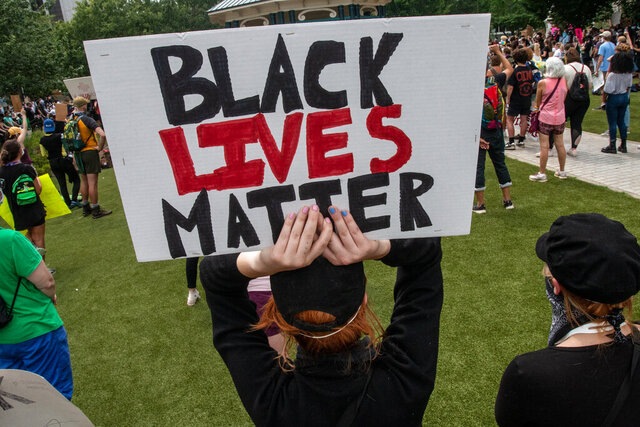 A woman holds a sign during a protest rally on Wednesday, June 3, 2020, in Decatur, Ga. The protest and rally at the town square brought out hundreds who chanted the name George Floyd and filled the streets demanding justice. (AP Photo/Ron Harris)