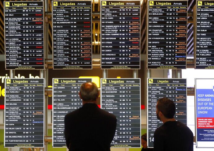 People look at their flight information shown at displays at the Adolfo Suárez-Barajas airport in Madrid, Spain, Monday, Feb. 3, 2020. Madrid's international airport was resuming air traffic after nearly two hours of airspace closure following the reported sighting of drones, Spanish authorities said Monday. (AP Photo/Paul White)