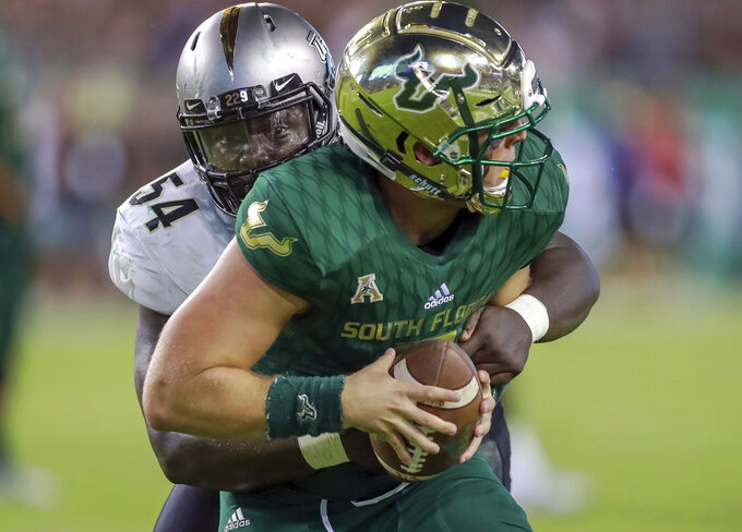 Central Florida's A.J. Wooten (54) sacks South Florida quarterback Brett Kean during the second half of an NCAA college football game Friday, Nov. 23, 2018, in Tampa, Fla. (AP Photo/Mike Carlson)