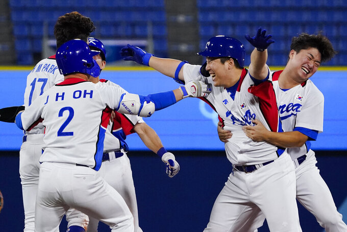 South Korea's Hyunsoo Kim, second right, celebrates with teammates his game winning RBI in the ninth inning of a baseball game against the Dominican Republic at the 2020 Summer Olympics, Sunday, Aug. 1, 2021, in Yokohama, Japan. South Korea won 4-3. (AP Photo/Sue Ogrocki)