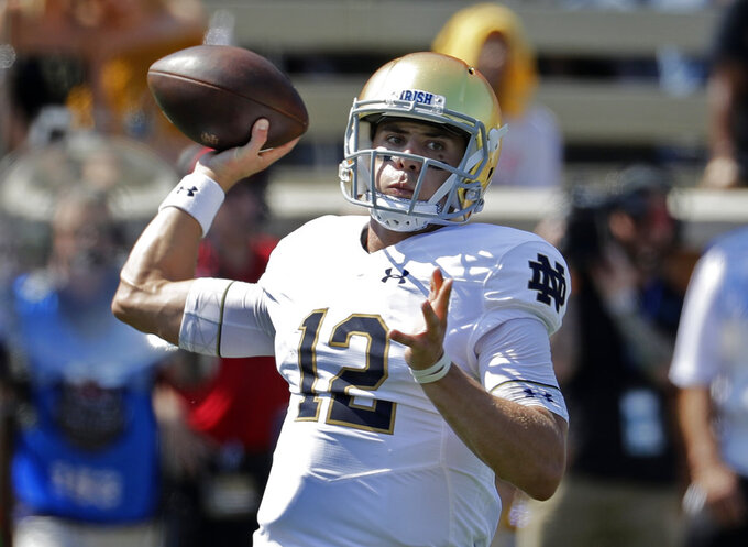 FILE - In this Sept. 22, 2018, file photo, Notre Dame's Ian Book (12) looks to pass against Wake Forest in the first half of an NCAA college football game, in Winston-Salem, N.C. Notre Dame (5-0) is seeking it's third win against a ranked team when they travel to Blacksburg, Va. to face No. 24 VirginiasTech (3-1) on Saturday.  (AP Photo/Chuck Burton, File)