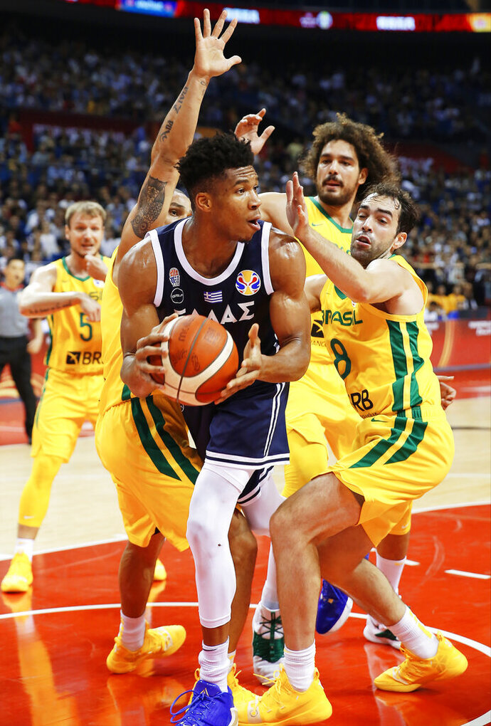 Giannis Antetokounmpo of Greece looks to pass around Vitor Benite of Brazil during their group stage match in the FIBA Basketball World Cup in Nanjing in eastern China's Jiangsu province, Tuesday, Sept. 3, 2019. (Chinatopix via AP)