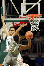 Miami center Rodney Miller Jr. (14) attempts to block a shot by Wake Forest guard Andrien White (13) during the first half of an NCAA college basketball game, Saturday, Feb. 15, 2020, in Coral Gables, Fla. (AP Photo/Wilfredo Lee)