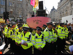 Police forces surround a boat at Oxford Circus in London, Friday, April 19, 2019. The group Extinction Rebellion is calling for a week of civil disobedience against what it says is the failure to tackle the causes of climate change. (AP Photo/Frank Augstein)