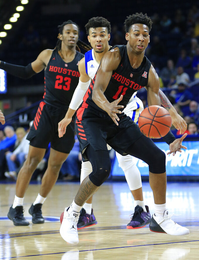 Houston's Nate Hinton (11) grabs the ball in front of Tulsa's Darian Jackson and Houston's Cedrick Alley, Jr. during the first half of an NCAA college basketball game in Tulsa, Okla., Sunday, Jan. 27, 2019. (AP Photo/Dave Crenshaw)