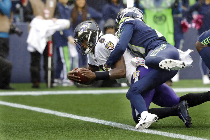 Baltimore Ravens quarterback Lamar Jackson (8) is hit by Seattle Seahawks cornerback Tre Flowers while scoring a touchdown on a fourth-down keeper play during the second half of an NFL football game, Sunday, Oct. 20, 2019, in Seattle. (AP Photo/Elaine Thompson)