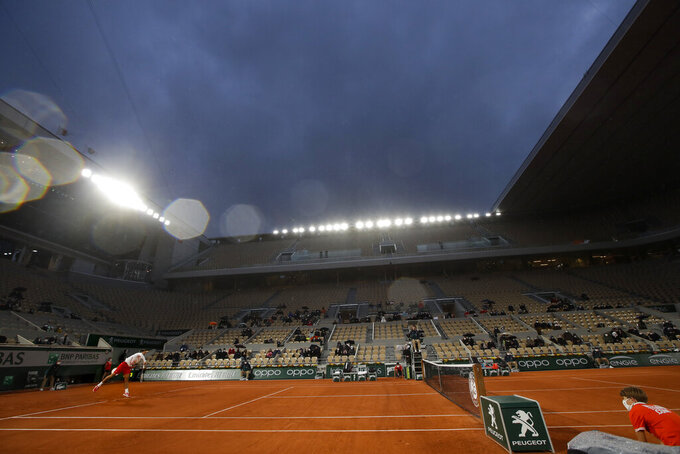 FILE - Light rain falls over center court as Serbia's Novak Djokovic, left, serves against Colombia's Daniel Elahi Galan in a third round match of the French Open tennis tournament at Roland Garros stadium in Paris, France, in this Saturday, Oct. 3, 2020, file photo. There will be night sessions at the French Open's main stadium for the first time this year. The tournament begins Sunday, May 30, 2021, in Paris. (AP Photo/Alessandra Tarantino, File)