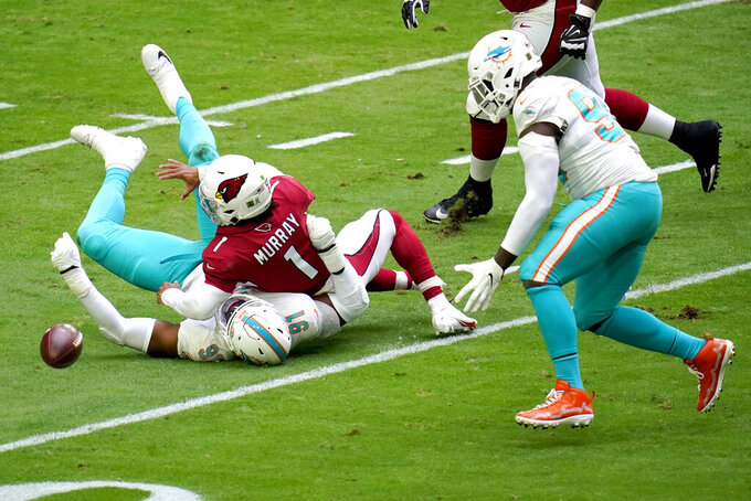 Miami Dolphins defensive end Emmanuel Ogbah (91) forces Arizona Cardinals quarterback Kyler Murray (1) to fumble during the first half of an NFL football game, Sunday, Nov. 8, 2020, in Glendale, Ariz. Dolphins' defensive end Shaq Lawson, right, recovered the ball for a touchdown. (AP Photo/Ross D. Franklin)