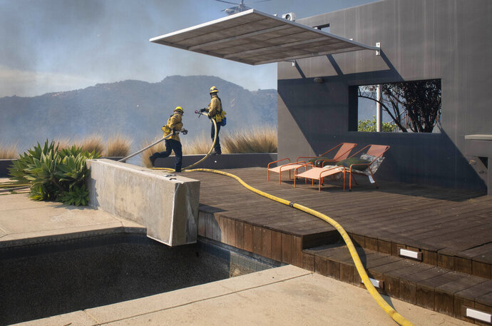 Firefighters protect a home from the flames of a wildfire in the Pacific Palisades area of Los Angeles, Monday, Oct. 21, 2019. (AP Photo/Christian Monterrosa)