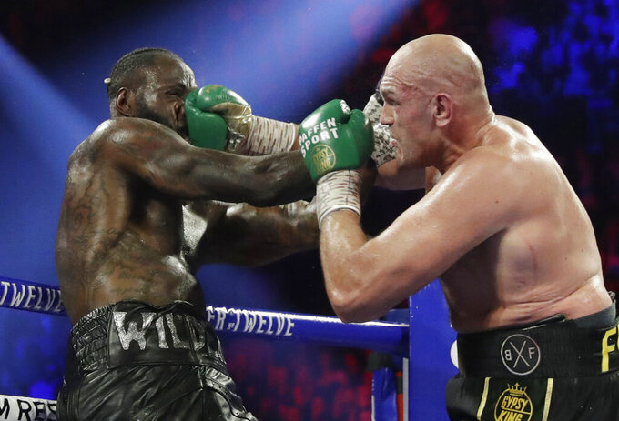 FILE - In this Feb. 22, 2020, file photo, Tyson Fury, of England, lands a right to Deontay Wilder, left, during a WBC heavyweight championship boxing match in Las Vegas. Boxing promoter Bob Arum says he plans to stage a card of five fights on June 9 at the MGM Grand. It's the first of a series of fights over the next two months at the Las Vegas hotel. A second fight card will be held two nights later. ESPN will televise both cards to kick off twice weekly shows at the hotel in June and July. The fights are pending approval of the Nevada Athletic Commission. (AP Photo/Isaac Brekken, File)