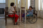Rafka Nassim, 71, right, meets with her daughter Claudette Rizk through a plastic barrier to avoid contracting the coronavirus, at the Social Services Medical Association, a rehabilitation hospital and nursing home in the northern city of Tripoli, Lebanon, Thursday, June 10, 2021. With virtually no national welfare system, Lebanon's elderly are left to fend for themselves amid their country's economic turmoil. (AP Photo/Hassan Ammar)
