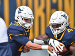 West Virginia quarterback Jarret Doege (2) hands off to running back Leddie Brown (4) during warmups before an NCAA college football game against Eastern Kentucky on Saturday, Sept. 12, 2020, in Morgantown, W.Va. (William Wotring/The Dominion-Post via AP)