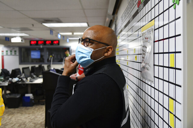 In this Thursday, April 16, 2020, photograph, Denver Mayor Michael Hancock wears a face mask as he listens to speakers at a morning briefing related to the coronavirus pandemic in the Emergency Operations Center in Denver. Hancock's days are filled with meetings. Questions and concerns pile up with each one as more residents are ignoring the stay-at-home order he put in place through the end of April to control the spread of the virus.  (Hyoung Chang/The Denver Post via AP)
