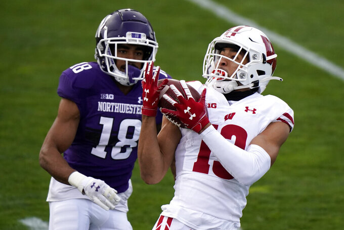Wisconsin wide receiver Chimere Dike, right, catches a pass against Northwestern defensive back Cameron Ruiz during the first half of an NCAA college football game in Evanston, Ill., Saturday, Nov. 21, 2020. (AP Photo/Nam Y. Huh)
