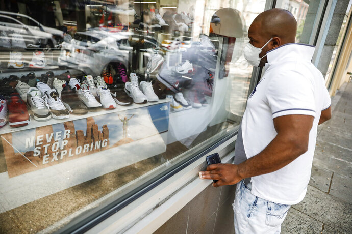 A pedestrian browses the display window at The Loop fashion and shoe store as businesses slowly begin to reopen after social distancing restrictions shuttered storefronts nationwide, Tuesday, May 26, 2020, in Yonkers, N.Y. (AP Photo/John Minchillo)