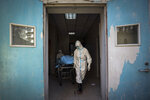 In this Sunday, Feb. 16, 2020, photo, medical workers move a person who died from COVID-19 at a hospital in Wuhan in central China's Hubei province. Chinese authorities on Monday reported a slight upturn in new virus cases and hundred more deaths for a total of thousands since the outbreak began two months ago. (Chinatopix via AP)