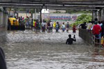 A man wades through a flooded underpass in Chennai, India, Wednesday, Nov.25, 2020. India's southern state of Tamil Nadu is bracing for Cyclone Nivar that is expected to make landfall on Wednesday. The state authorities have issued an alert and asked people living in low-lying and flood-prone areas to move to safer places. (AP Photo/R. Parthibhan)