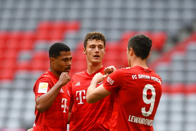 Munich's Benjamin Pavard, center, Serge Gnabry, left, and Robert Lewandowski celebrate after scoring during the German Bundesliga soccer match between FC Bayern Munich and Fortuna Duesseldorf in Munich, Germany, Saturday, May 30, 2020. Because of the coronavirus outbreak all soccer matches of the German Bundesliga take place without spectators. (Christof Stache/Pool via AP)