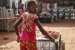 In this Wednesday, May 13, 2020, photo, a girl pushes a cart of food at a market in Tougan, Burkina Faso. Violence linked to Islamic extremists has spread to Burkina Faso's breadbasket region, pushing thousands of people toward hunger and threatening to cut off food aid for millions more. (AP Photo/Sam Mednick)