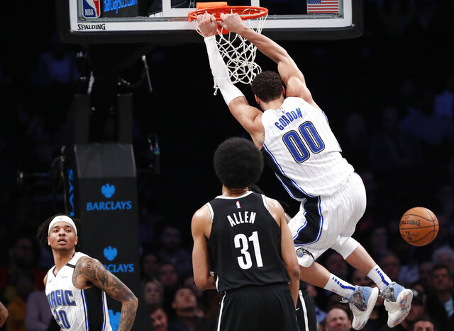 Orlando Magic guard Markelle Fultz (20) watches as Magic forward Aaron Gordon (00) dunks in front of Brooklyn Nets center Jarrett Allen (31) during the second quarter of an NBA basketball game, Monday, Feb. 24, 2020, in New York. (AP Photo/Kathy Willens)