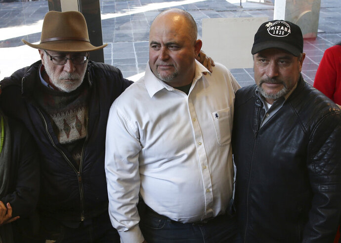 Mexican writer and activist Javier Sicilia, left, Julian, center, and Adrian LeBaron, who lost relatives and friends in a Nov. 4, 2019 ambush in northern Mexico, pose for photos during a press conference in Mexico City, Thursday, Jan. 9, 2020. Sicilia and other activists are calling to march against violence on Jan. 23, from Cuernavaca, Morelos state, to the National Palace in the Mexico's capital. (AP Photo/Marco Ugarte)