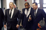 FILE — In this Jan. 25, 2019, file photo, Harvey Weinstein, left, enters court with attorneys Ron Sullivan, center, and Jose Baez, in New York. Weinstein is suing his one-time lawyer, Baez, for breach of contract and is seeking a refund on $1 million in legal fees he says he paid the high-profile attorney for a short stint on his legal team. (AP Photo/Mark Lennihan, File)