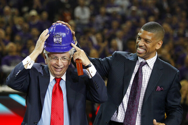 FILE - In this Oct. 30, 2013, file photo, Sacramento Mayor Kevin Johnson, right, helps NBA Commissioner David Stern put on a hard hat presented to him during ceremonies at the Kings NBA basketball game against the Denver Nuggets, in Sacramento, Calif. David Stern was a guy in the big city who did some of his best work fighting for the little guys. Teams in cities such as Sacramento and New Orleans might be playing elsewhere if not for the efforts of the former NBA commissioner who died Wednesday, Jan. 1, 2020. (AP Photo/Genevieve Ross, File)