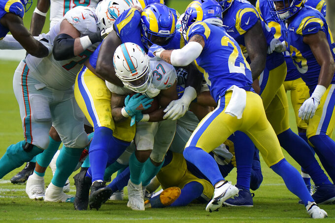 Los Angeles Miami Dolphins running back Myles Gaskin (37) is tackled by Los Angeles Rams safety Taylor Rapp (24) and middle linebacker Micah Kiser (59) during the second half of an NFL football game, Sunday, Nov. 1, 2020, in Miami Gardens, Fla. (AP Photo/Wilfredo Lee)
