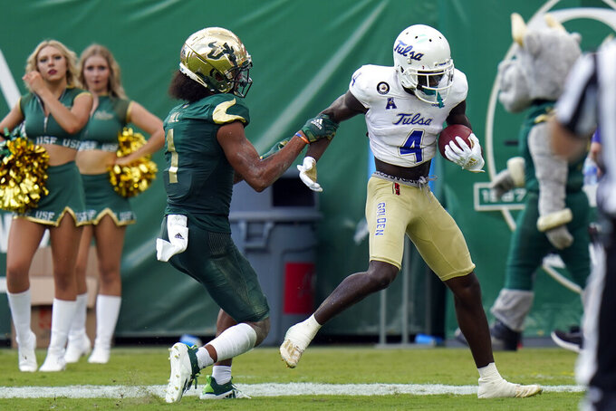 Tulsa wide receiver Josh Johnson (4) scores in front of South Florida safety Matthew Hill (1) during the second half of an NCAA college football game Saturday, Oct. 16, 2021, in Tampa, Fla. (AP Photo/Chris O'Meara)