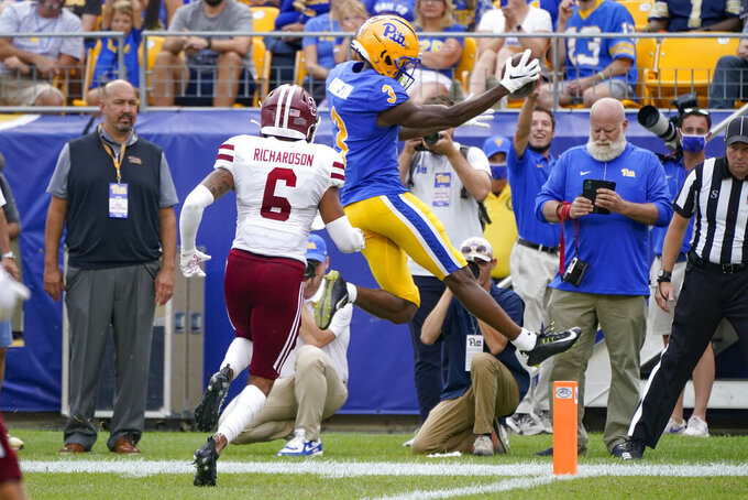 Pittsburgh wide receiver Jordan Addison (3) leaps for the end zone past Massachusetts defensive back Bryson Richardson (6) for a touchdown after making a catch during the first half of an NCAA college football game, Saturday, Sept. 4, 2021, in Pittsburgh. (AP Photo/Keith Srakocic)
