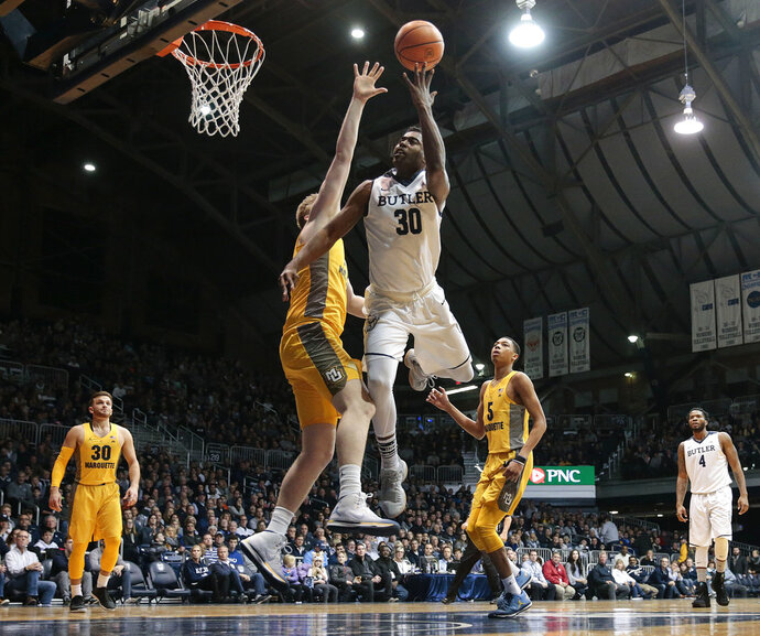 Butler forward Kelan Martin, center, shoots around Marquette center Harry Frolin, left, during the first half of an NCAA college basketball game in Indianapolis, Friday, Jan. 12, 2018. (AP Photo/AJ Mast)